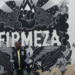 Lucas Pereira na frente de um graffiti