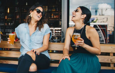 Two women laughing and drinking beer