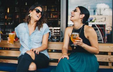 Dos mujeres riendo y tomando una cerveza